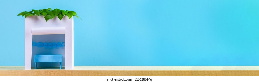 Banner. Happy Sukkot. A hut made of paper covered with leaves on a blue background. Copy the space.