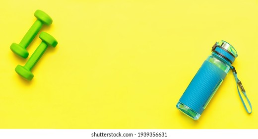 Banner. Healthy lifestyle. Sports blue water bottle and two green dumbbells isolated on yellow background. Sport equipment. Fitness concept. Copy space for design