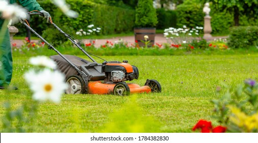 Banner. A human lawn mower cuts the grass in the backyard. Agricultural machinery for the care of the garden.