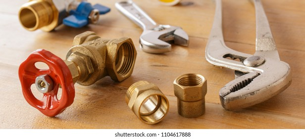 Banner image of an adjustable spanner, a vice grip, and water valves on wooden surface