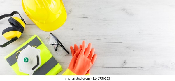 Banner image of construction safety gear including a hard hat, folded reflective jacket, face mask, goggles, and rubber gloves flat lay on white wooden surface with copy space