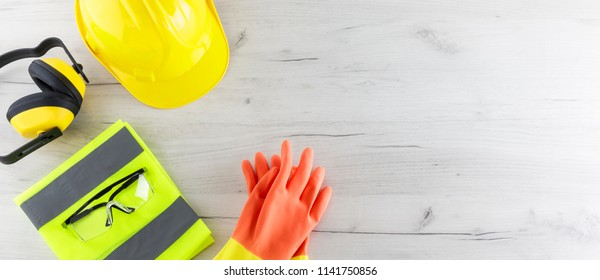 Banner image of construction safety gear including a hard hat, folded reflective jacket, goggles, and rubber gloves flat lay on white wooden surface with copy space