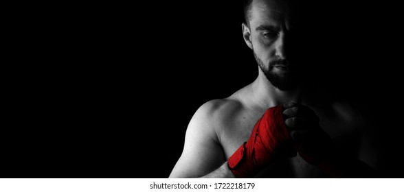 Banner image of a man's fighter with a beard and red bandages on his hands. Black white image with red. Place for text. Black background.