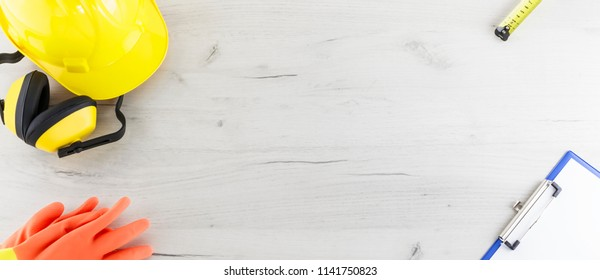 Banner image of hard hat, earmuffs, gloves, tape measure, and a clipboard flat lay on a white wooden background
