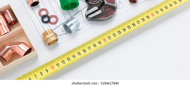 Banner image of plumbing materials including copper elbow joints, washers, and couplers with pipe wrench and tape measure with copy space