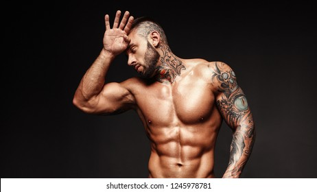 Banner image of sexy man with muscular body. Portrait of sexi male model. Hot macho, bodybuilder with muscle torso in abs poses on black background. 16 in 9 crop for design.