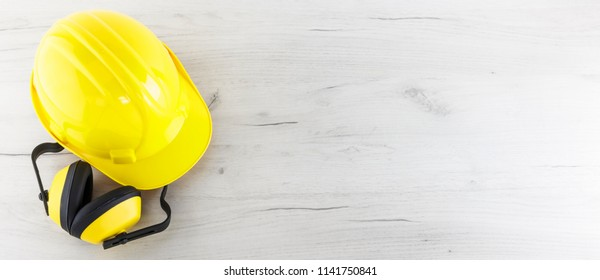 Banner image of yellow hard hat and earmuffs on white wooden background with copy space