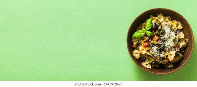 banner of italian pasta butterflies with sicilian vegetable caponata in a clay plate on a green background