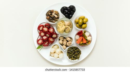 banner of Italian traditional pickles on a plate. tuna stuffed peppers, artichokes in oil, olives, mushrooms, capers. copy space.