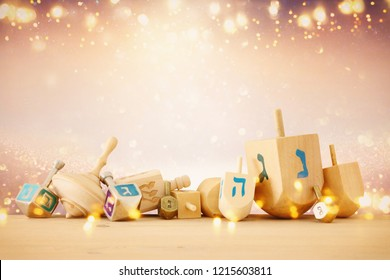 banner of jewish holiday hanukkah with wooden dreidels spinning top over glitter shiny background