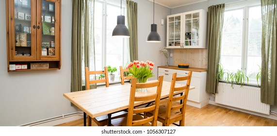 banner of a kitchen with green curtains and kitchen table