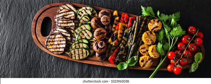 banner. a large portion of colored grilled vegetables and mushrooms on a wooden tray on a dark slate. festive summer food