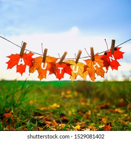 banner with letters and the name autumn carved on red maple leaves hanging on clothespins and rope in an autumn Sunny Park against a clear sky
