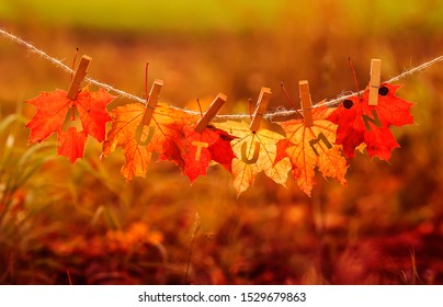 banner with letters and the name autumn carved on red maple leaves hanging on clothespins and rope in the autumn clear Sunny Park