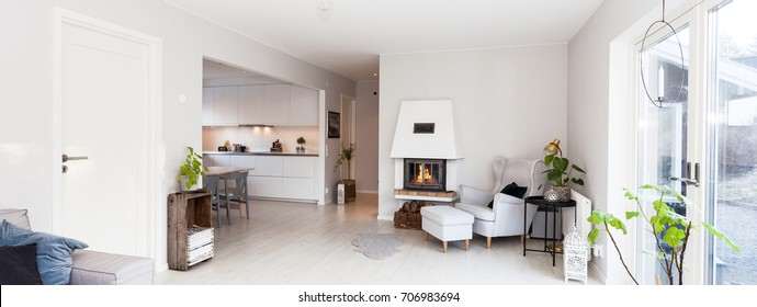 banner of a living room and kitchen with a relaxing chair by the lit fireplace