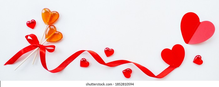 Banner.Two lollipops, red ribbon and hearts on a white background. Red hearts. Candy Love concept. Valentine's Day. Copy space for inscriptions.