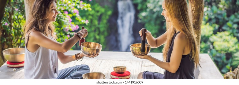 BANNER, LONG FORMAT Nepal Buddha copper singing bowl at spa salon. Young beautiful woman doing massage therapy singing bowls in the Spa against a waterfall. Sound therapy, recreation, meditation