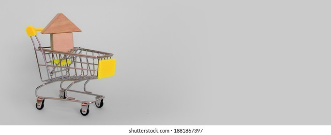 Banner of a model of a wooden makeshift house in a grocery cart with a yellow handle on a gray background. Horizontal format. Side view. Copyspace