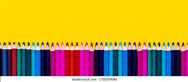Banner with multicolored wooden pencils on yellow background. Large format. Bottom border. Education concept. School supplies.