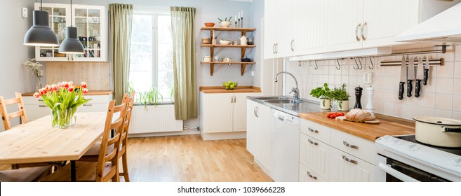 banner ofa kitchen with tulips on the table and white cupboards, food on the kitchen counter top