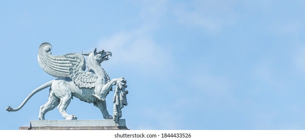 Banner with old statue of medieval griffin, a hybrid of lion and bird, on the top of the State Opera House in downtown of Dresden, Germany, details, closeup, with copy space for text
