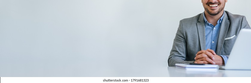 Banner panorama of faceless mid body section young smiling cheerful businessman entrepreneur in bright white modern office facing towards camera copy space for text