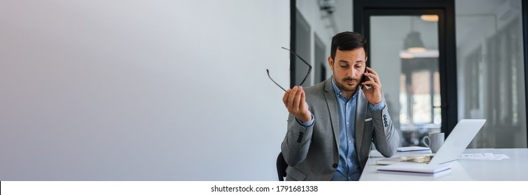Banner panorama of stressed out troublesome businessman in office making important phone call about serious problem working under pressure and tight deadline receiving bad market news recession copy
