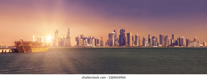 Banner panorama of traditional wooden dhow and towers of the West Bay skyline with sunset sun rays in Doha Bay. Capital of Qatar, Middle East, Persian Gulf. Urban cityscape. Wallpaper background.