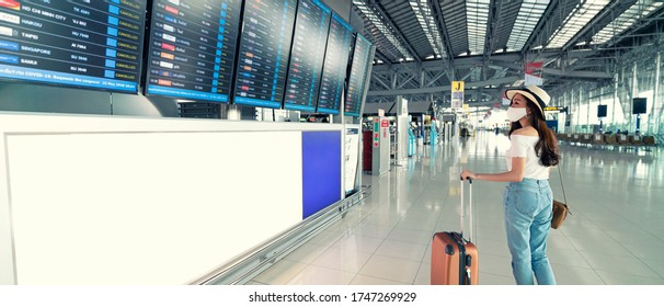 Banner photo of Asian female wearing face mask with suitcase checking flight cancellation status on airport information board in empty airport. airline bankrupt, airline crisis or new normal concept
