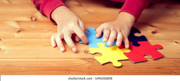 Banner picture of an autistic child's hands playing a puzzle symbol of Public awareness for autism spectrum disorder. World Autism Awareness day April 2, Supportive, Understanding and Acceptance.