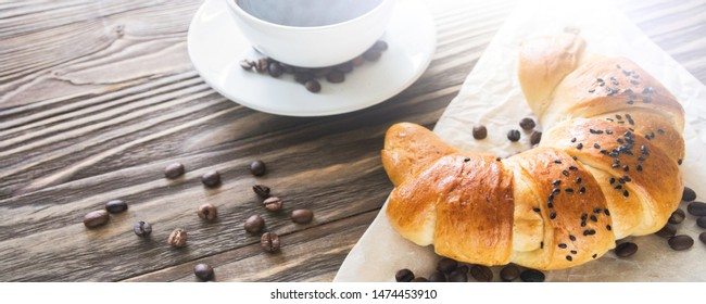 Banner with a picture of a croissant, a Cup of instant coffee and coffee beans on a textured wooden background top view, cozy and delicious Breakfast. Lighted rustic background.
