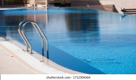 Banner. The pool with bright blue water and a metal staircase in the hotel.