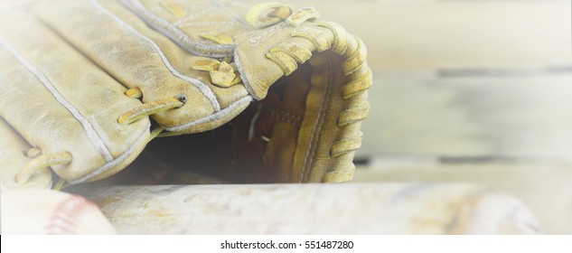 Banner shaped image of old leather baseball mitt, or glove, and bat on wooden background. White vignette added.
