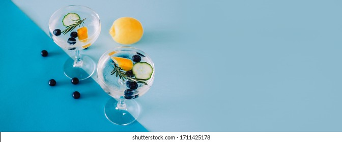 Banner showing two glasses of Gin and tonic cocktails with cucumbers, lemon and blueberries isolated on geometric blue coloured background