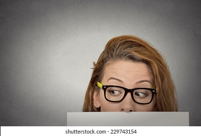 Banner sign woman peeking over edge of blank empty paper billboard. Beautiful young girl with glasses looking to side surprised curious scared funny interested open eyes isolated grey wall background