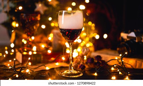 Banner size 16 in 9. Festive atmosphere with a glass of red wine. Smoke creeping in glass and light bokeh background. Christmas, New Year's or Saint Valentine holiday.Golden color and soft focus.