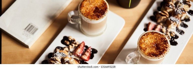 Banner size image of two cups of Hot latte with baked caramel crust and sweet roll with banana and strawberry on the wooden table in coffe-shop. Coffee concept.