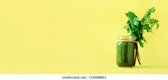 Banner of smoothie with beet greens and carrot tops on yellow background, copy space. Summer vegan food concept. Healthy detox eating, alkaline diet. Fresh juice, drink from vegetables. Leafy greens