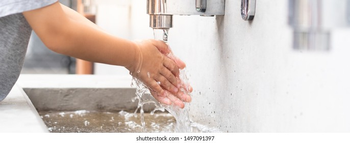 Banner of a student boy wash hands at the outdoor wash basin in the school. Preventing Contagious diseases, Plague. Kids health, Hygiene, Flu, H5N1 influenza, Saving water, Covid-19, New normal.