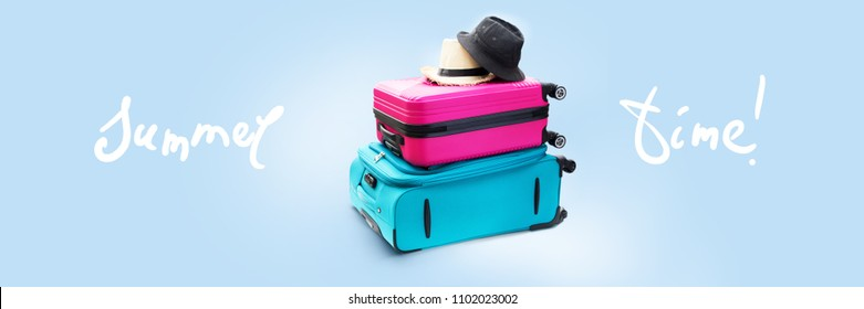 Banner Summer Time Blue and Pink Trunks Straw and Fabric Hats. Two Suitcases Luggage Travel. Concept Holiday Adventure Trip. Isolated on Blue Background