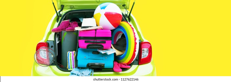 Banner Summer Travel Time Overloaded Green Car Blue and Pink Trunks Straw Hat Slippers Rackets Towels Rug Yoga Two Suitcases Luggage Holiday Concept Adventure Trip. Isolated on Yellow Background