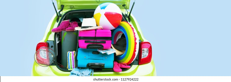 Banner Summer Travel Time Overloaded Luggage Carrier Gren Car Blue and Pink Trunks Straw Hat Slippers Rackets Towels Rug Yoga Two Suitcases Holiday Concept Adventure Trip. Isolated on Blue Background