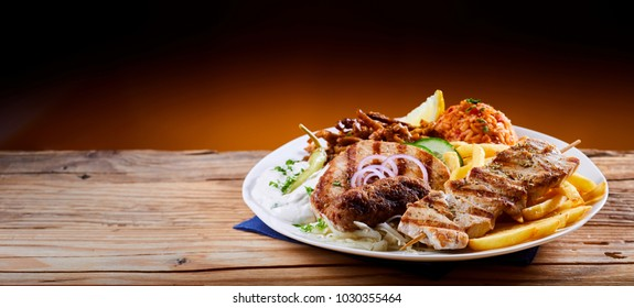 Banner with a traditional Greek mixed grill platter served with tomato rice, French Fries and cool refreshing raiti yogurt on a rustic table with copy space