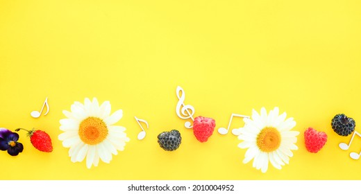 banner treble clef and music notes with flowers and berries on a yellow background. summer music concept.