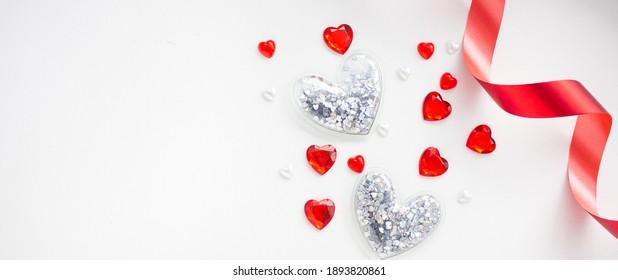Banner. Valentinstag. Flache Lagen aus roten und silbernen Herzen und rotem Band auf weißem Hintergrund. Kopiert Platz. Das Konzept von Urlaub und Liebe.