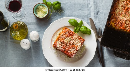 banner of vegan lasagna with lentils and green peas in a baking sheet on a table with a blue linen tablecloth. healthy Italian cuisine for the whole family, party or restaurant and red wine in glasses