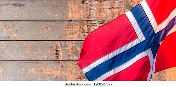 Banner with waving Norwegian flag on the old wooden pattern background with copy space