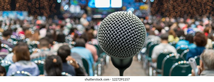 Banner and web page or cover template of Microphone over blurred photo of conference hall or seminar room in Exhibition Center background with Speakers on the stage and attendee background