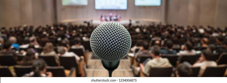 Banner and web page or cover template of Microphone over the Abstract blurred photo of conference hall or seminar room with attendee background, Business meeting concept
