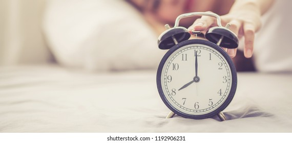 Banner website beautiful asian young woman turn off alarm clock in good morning, wake up for sleep with closeup foreground alarm clock, relax and lifestyle concept.